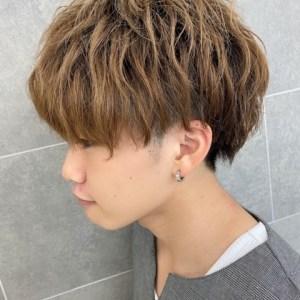 前髪は目にかかる程の長さで後頭部が刈りあがっているヘアスタイル