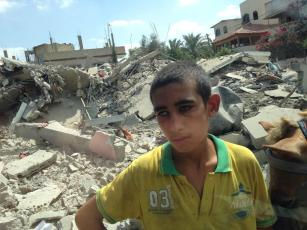 Gaza - 26 July boy stands amid rubble in Beit Hanoun