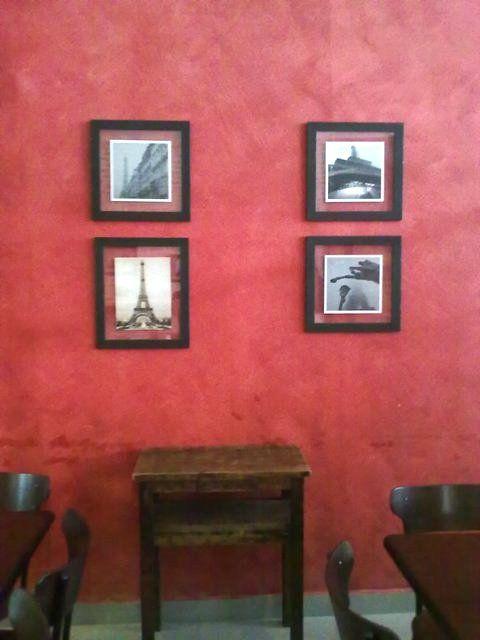 Decoração: parede vermelha com quadros de fotos em preto e branco