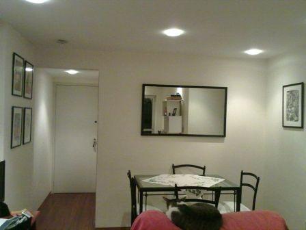 Sala com quadro, espelho e piso de madeira