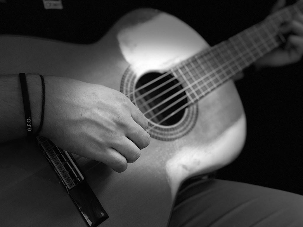 Close-up view of person playing acoustic guitar