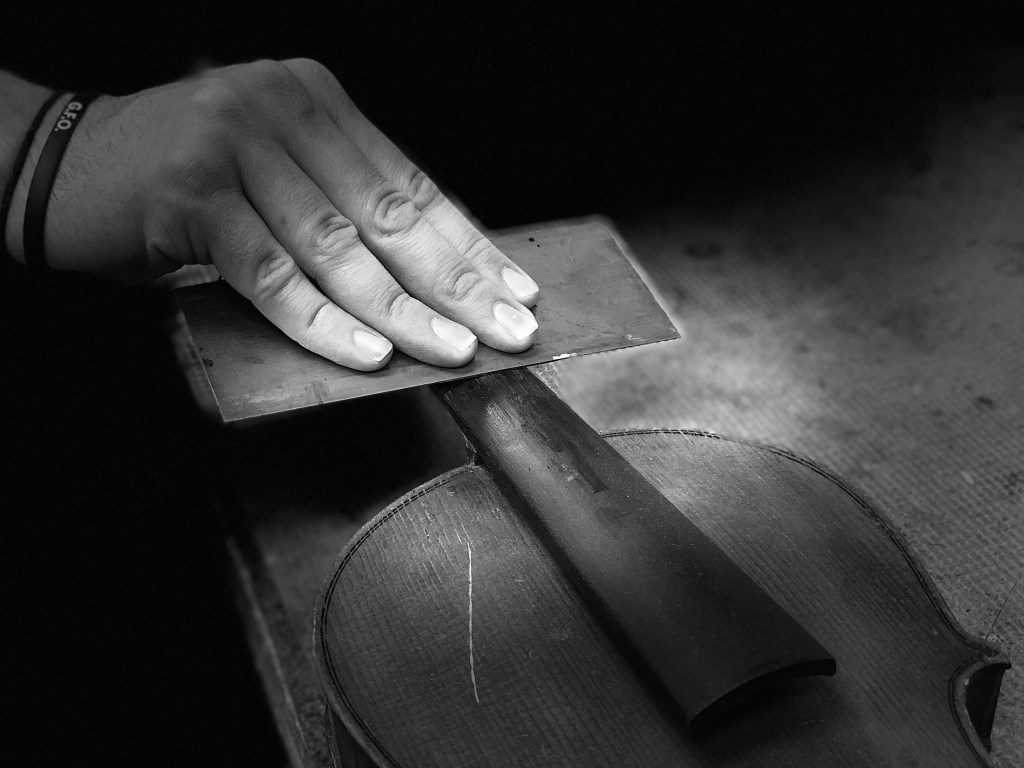 Close-up view of instrument technician working on a violin neck
