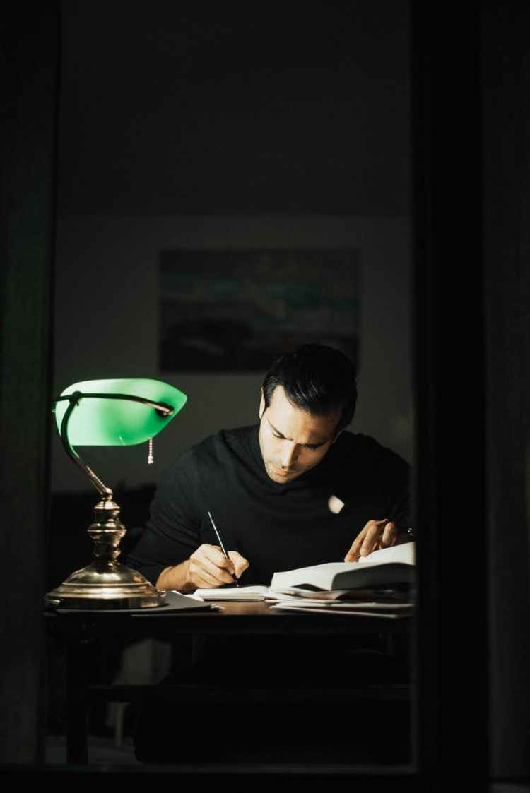 thoughtful man writing in notebook and studying in home office