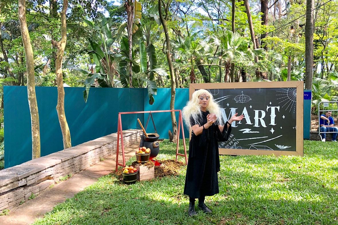 Artista circense com produção de bruxa e com esfera crystall de contato interagindo com o público da convenção empresarial Bloomberg, evento com temática surreal realizado na Fundação Oscar Americano em SP.