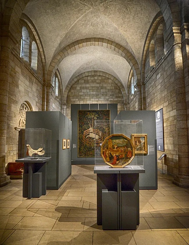 Unicorn objects on display under the stone arches of The Cloisters building