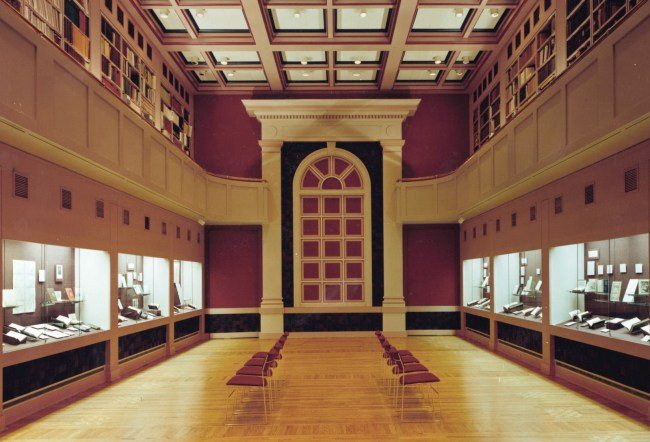 A photograph of a two story hall with display cases set in the lower story wall s and bookshelves in the gallery above.