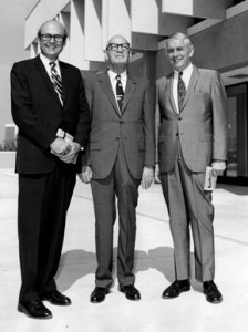 Three men in suits stand in front of a building.