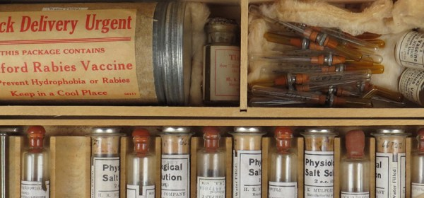 A divided wooden box containing syringes, ampules and a metal canister of vaccine.