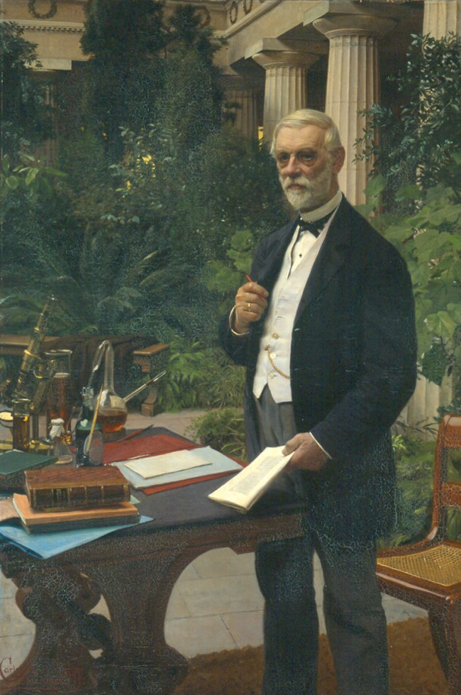A man stands holding a pen and journal at a table covered with books, a cmicroscope and chemical equipment including a pasteur flask.