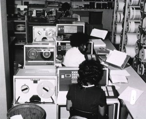 Operators are sitting in front of data entry computers. Rolls of tapes are shelved to the right of the computers.