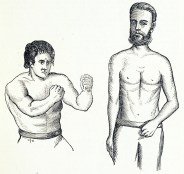 A heavily muscled man in a boxing pose stands next to a taller, more slim man.