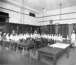 Twenty-eight boys lined up around a room waiting in turn to be seen by a nurse.
