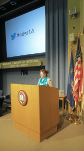 A speaker at the podium, behind her the twitter hastag for the conference, #ndsr14, is projected on a screen.