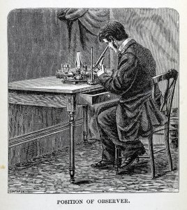 A man sits at a table looking into a microscope.
