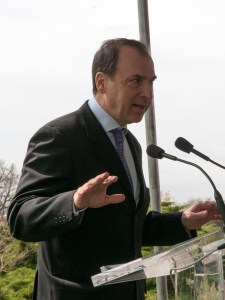 His Excellency, Christos P. Panagopoulos speaks at a podium on the lawn of the National Library of Medicine.