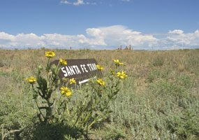 A painted wooden sign reading Santa Fe Trail sits on the prarie, with blue sky above and yellow wildflowers in the foreground.
