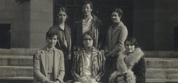 Six young women pose on the steps of a building.