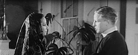 Still from a black and white film, a priest speaks to a woman in a headscarf.