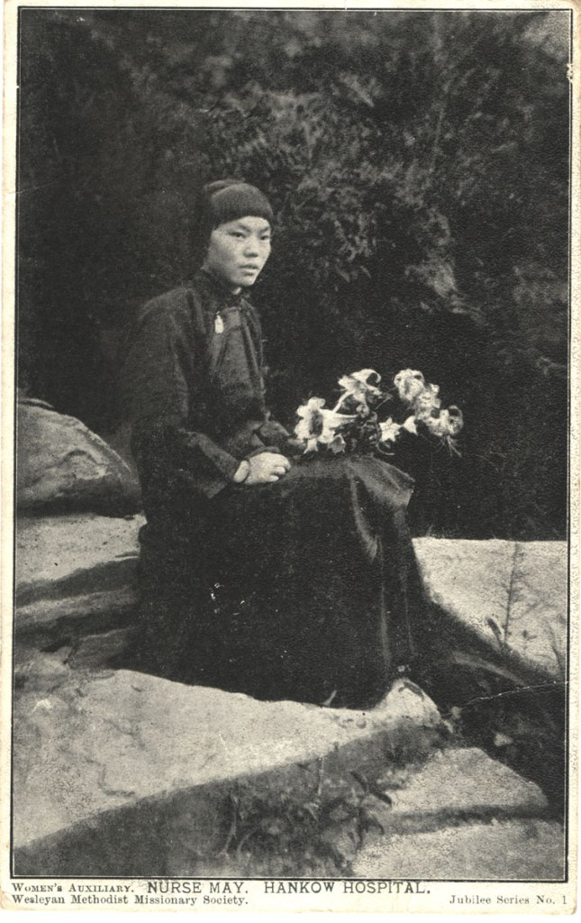 An Asian woman in long dark clothing sits oudoors on a rock holding a bunch of lilies.