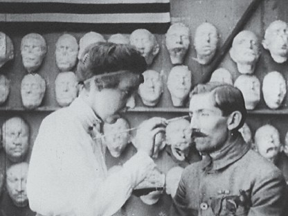 In front of a wall covered in masks a woman paints a mask worn by a man.