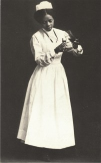 An African American nurse in white stands and pours liquid from one container to another.