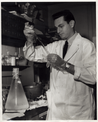 A young man in a lab coat and plastic gloves holds up a glass tube in a laboratory.