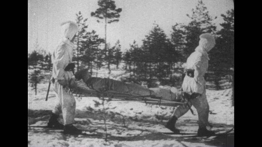 Two figures in white uniforms and on skis, carry an injured patient on a strectcher through the snow covered landscape.