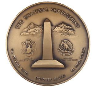 A medal with an obelisk in the center and the seals of the USA and Mexico.