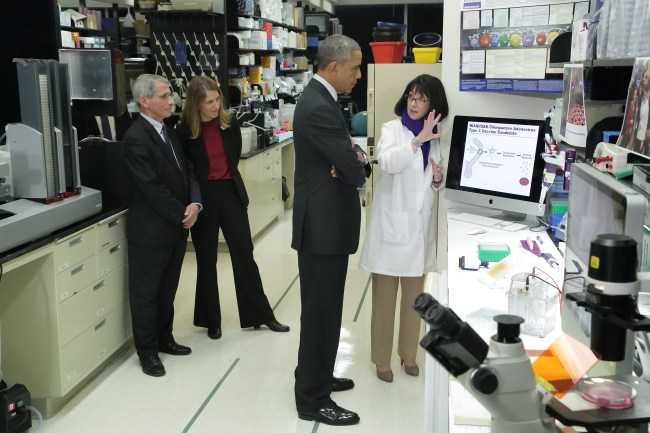 Obama stands in a lab listening to Dr. Nancy Sullivan explain.