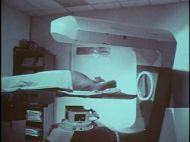 A still from a film showing a man lying in a large medical machine.