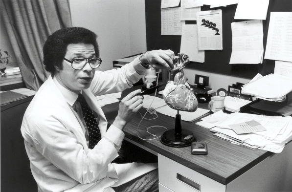 Man seated at a desk with a model of the heart on the desk.