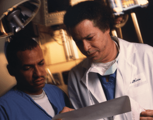 Dr. Levi Watkins Jr. on right, confers with anesthesiologist Jackie Martin. Both men are in blue surgical scrubs while Dr. Watkins has a surgical mask around his neck and wearing a white doctor's lab coat.