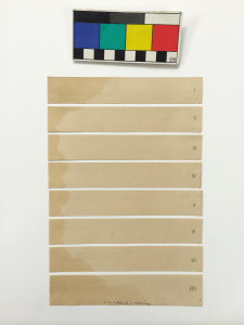 A piece of paper with one edge darkened irregularly by oil, cut horizontally into 8 numbered slips.