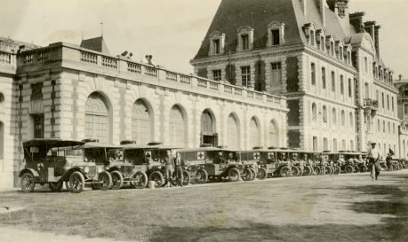 A line of 20 or so WWI era ambulances in front of a large building.