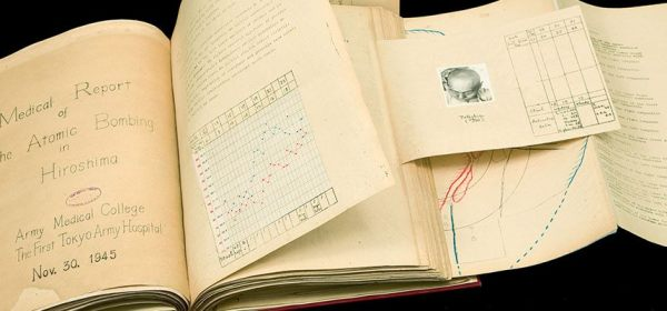 A report, assembled like a scrapbook, with typed pages and attached tabes, graphs, and photographs.