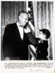 A boy in a cub scout uniform reaches up to Fogarty's lapel as they stand in front of an American flag.