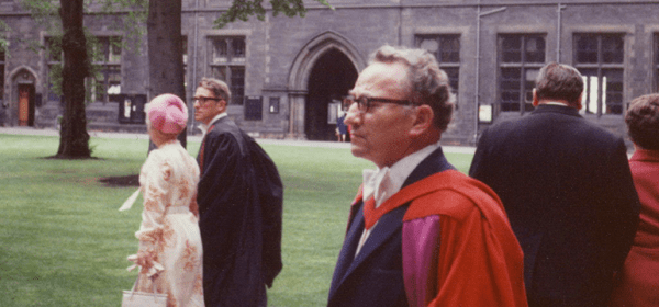 Spiegelman in his middle years stands informally outside a university buidling in academic robes.