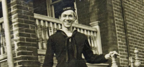 A man in a naval uniform poses outside a brick building.