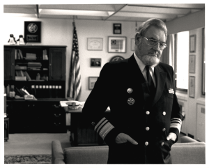 Dr. Koop in uniform, an american flag is in the background.