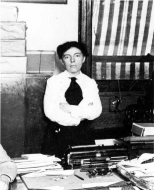 A woman stands with her arms crossed behind a desk with a typewriter on it.