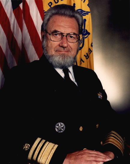 A formal portrait in uniform with the American flag.