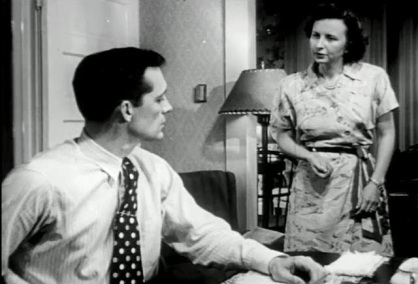 In a home, a woman speaks to a man seated at a desk.