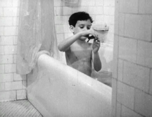 A boy plays with a live turtle in a bathtub.