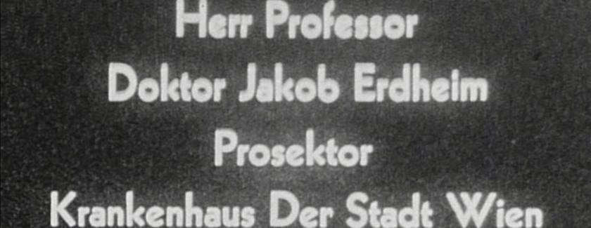 Grainy still from film that reads: Herr Professor Doktor Jakob Erdheim Prosektor Krankenhaus Der Stadt Wien
