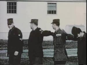 Men in uniform perform a drill.