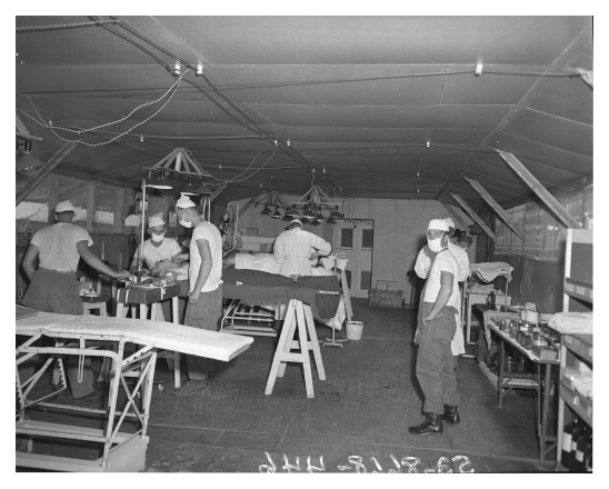 An operating tent where military surgions are working on two patients.