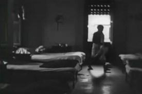 A man walks through a dormatory room.