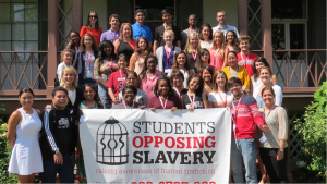 A group of about 3o young people posed on steps holding a banner.