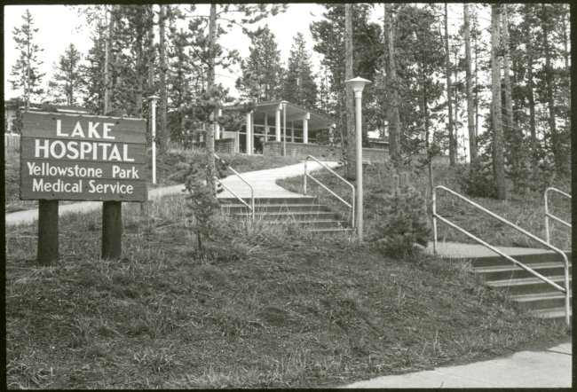 A sign reading Lake Hospital Yellowstone Park Medical Service stands by concrete stepsleading though trees to a building in the distance.