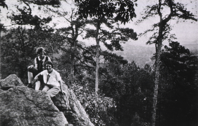 Two women sit on rocks surrounded by wooded hills.